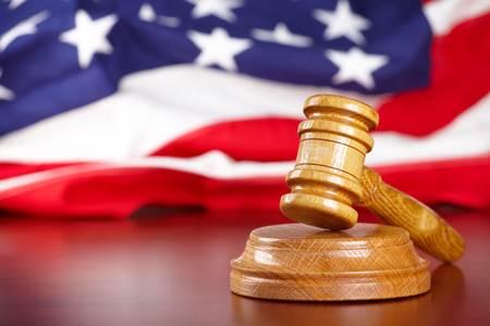 court order: Martillo de madera de jueces con bandera de Estados Unidos en segundo plano
