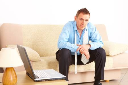 Tired businessman sitting on sofa after long day of work. Laptop computer on the left.
