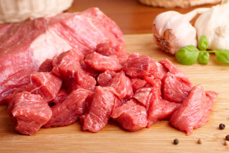 goulash: Fresh raw beef on wooden cutting board with garlic, pepper and bazil