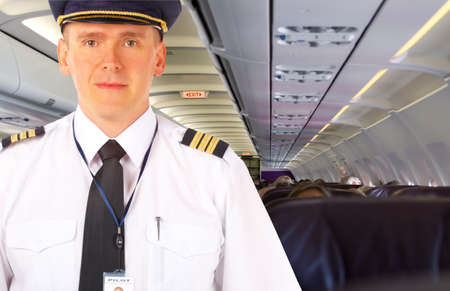 Airline pilot wearing uniform with epaulettes and hat, on board passenger aircraft.  Stock Photo