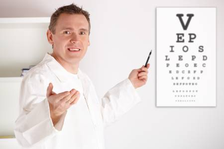 hyperopia: Male oculist doctor examining patient with an eye chart behind him.