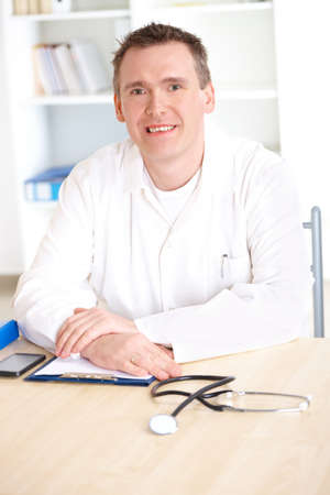 Cheerful medical doctor with stethoscope sitting at a desk in his office  Stock Photo - 8987835