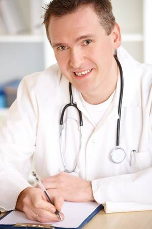 Smiling medical doctor with stethoscope sitting at a desk in his office and taking notes. Stock Photo - 8987864