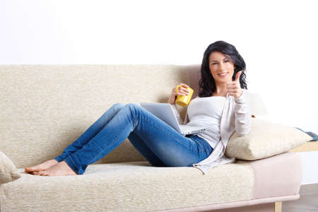 Beautiful young woman relaxing on sofa with laptop and a cup of tea showing thumb up in home  photo