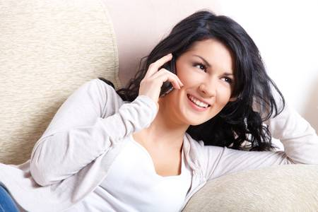 Beautiful young woman talking on the phone laying on the sofa Stock Photo - 9502657