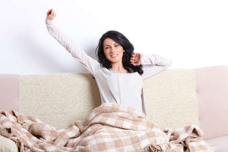 despertarse: Hermosa mujer que se extiende su cuerpo despu�s de que ella despierta en el sof� de casa Foto de archivo