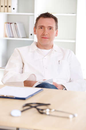 Cheerful medical doctor with stethoscope sitting at a desk in his office Stock Photo - 9679209