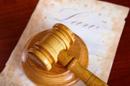Judges wooden gavel with old paper with word law in the background. Stock Photo - 9679222