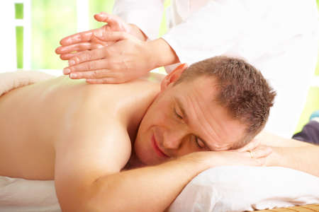 Man enjoying massage treatment with female hands on his back photo
