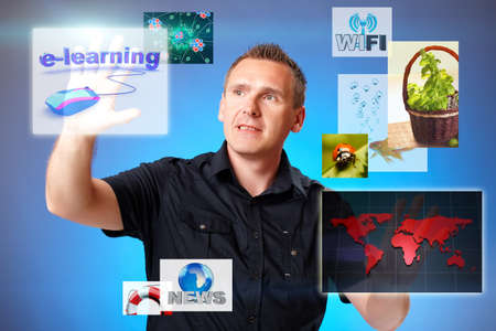 Man pressing screen with e learning, other displays with miscelenious subjects flying around. Stock Photo
