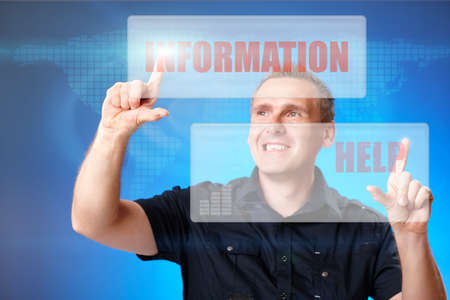 Man using holographic interface, pressing white and red buttons with words information and help Stock Photo - 9816390