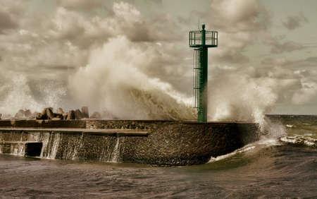 Huge storm wave crashed against the breakwater near the seaport photo