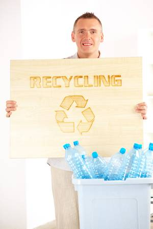 Happy man holding wooden board with word recycling and bin full of plastic blue bottles Stock Photo - 10101415