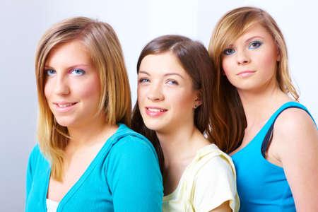 Three beautiful girls standing in a row photo