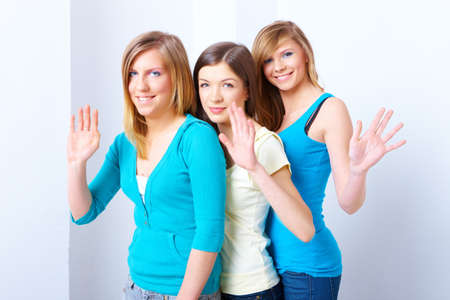 Three beautiful girls standing in a row and waving photo