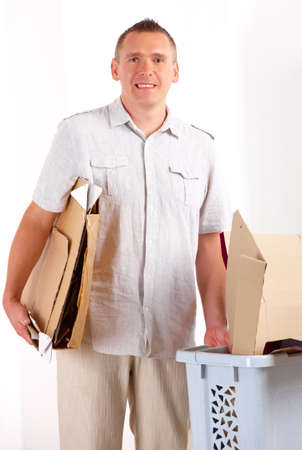 Happy man holding cardboard and bin full of paper  photo