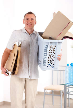 Happy man holding recycling bin full of paper photo