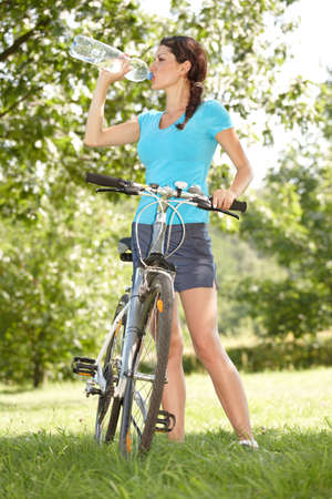Young woman biker thirsty drinking water photo