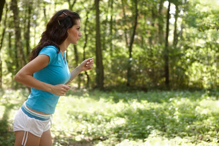 Young woman running in the park listening to music Stock Photo - 11194130