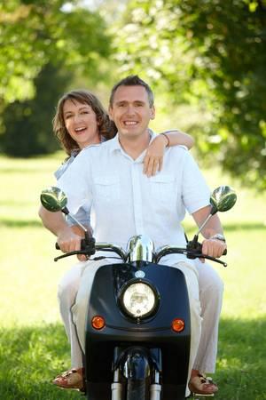 Couple ride retro motorbike scooter  photo
