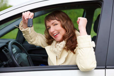Beautiful happy woman sitting in a car and showing keys out the window photo