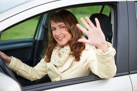Pretty young woman sitting car looking out of window, waving and smiling  photo