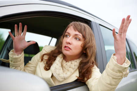 bad hair: Angry young woman stuck in a traffic jam Stock Photo