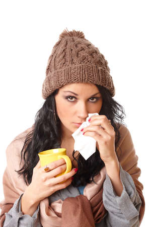 symptom: sad young woman with flu symptom holding a mug with a hot drink isolated on white background