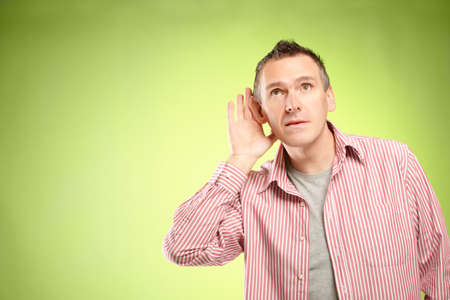 Man listening with hand on ear photo