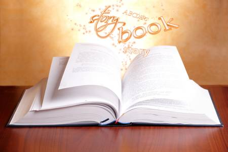 Open book laying on a table with flying words Stock Photo - 11844415