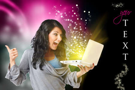Young happy woman with laptop computer and modern design in background, black space on right for your text and glitters you can use.