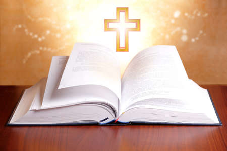 biblia: Santa Biblia abierta con luz tranquila y la cruz Foto de archivo