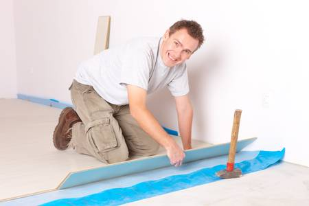 Happy manual worker installing a laminated flooring Stock Photo - 11844434