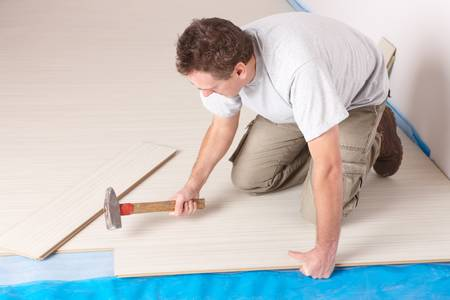Happy manual worker installing a laminated flooring