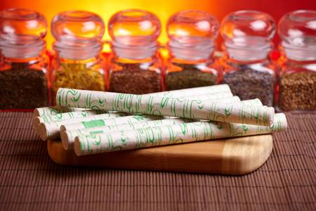 moxibustion: Professional moxa sticks on wooden desk with TCM herbs in glass jars in background