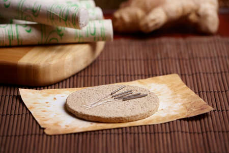 moxibustion: Acupuncture needles laying on the stone mat, moxa sticks on wooden desk and fresh ginger in the background. TCM Traditional Chinese Medicine concept photo