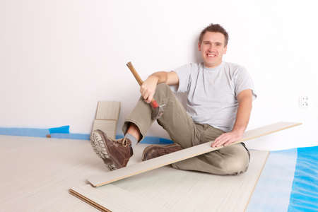 Happy manual worker installing a laminated flooring photo