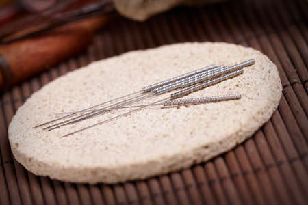 Acupuncture needles laying on the stone mat, TCM Traditional Chinese Medicine concept photo