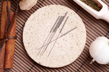 alternative medicine: Acupuncture needles laying on the stone mat and herbs like garlic. TCM Traditional Chinese Medicine concept photo