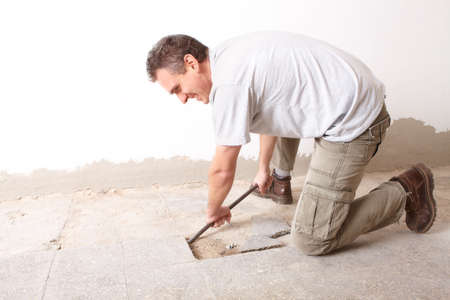 Happy manual worker disassembling old floor tiles photo