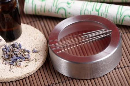 eastern health treatment: Acupuncture needles laying on the stone mat, moxa sticks on wooden desk and lavender petals with macerated oil. TCM Traditional Chinese Medicine concept photo