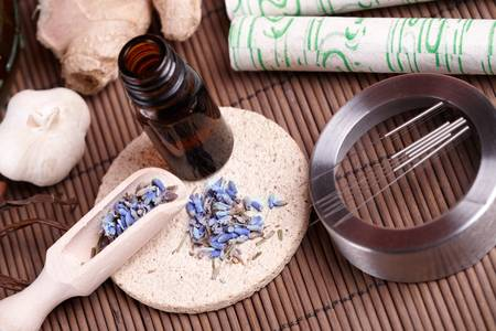 moxibustion: Acupuncture needles laying on the stone mat, moxa sticks on wooden desk and lavender petals with macerated oil. TCM Traditional Chinese Medicine concept photo