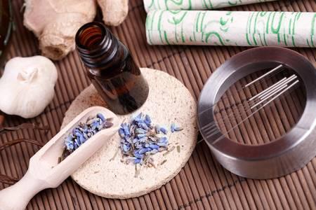 acupuntura china: Las agujas de acupuntura que están en el tapete de piedra, palos de moxa en el escritorio de madera y los pétalos de lavanda con aceite macerado. MTC Medicina Tradicional China de fotos concepto Foto de archivo