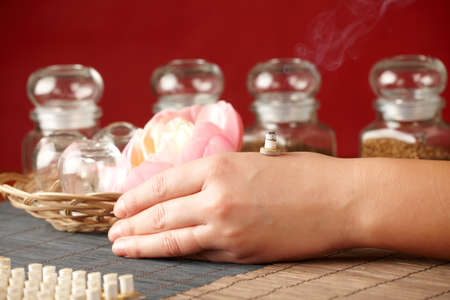 moxibustion: TCM Traditional Chinese Medicine. Smoking mini moxa stick, flower and natural herbs in glass jars in background.