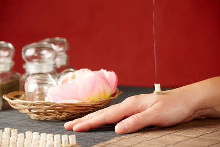 TCM Traditional Chinese Medicine. Smoking mini moxa stick, flower and natural herbs in glass jars in background. Stock Photo - 11956972