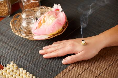eastern health treatment: TCM Traditional Chinese Medicine. Smoking mini moxa stick, flower and natural herbs in glass jars in background.