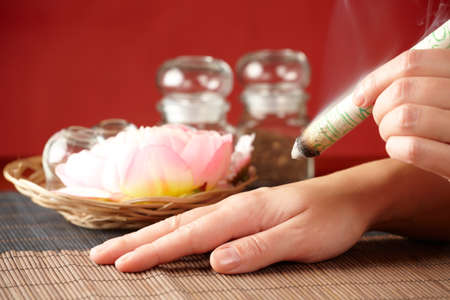 moxibustion: TCM Traditional Chinese Medicine. Hand applying moxa stick therapy, natural herbs in glass jars in background