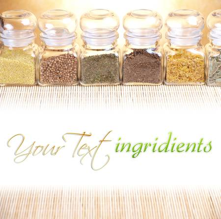Kitchen glass jars with ingridients dried spices, herbs like savory, coriander and other with white copy space for your text