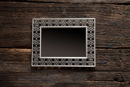 Metal frame with empty space for your image over old wooden background wall photo
