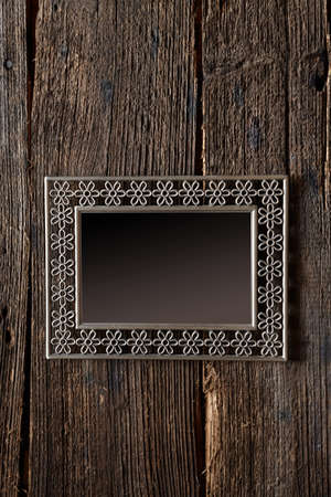 Metal frame with empty space for your image over old wooden background wall Stock Photo